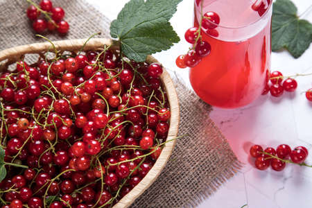 Sprigs of red currant berries are lying in a wicker plate, a Morse of berries is in a glass glass on a light background Stock Photo