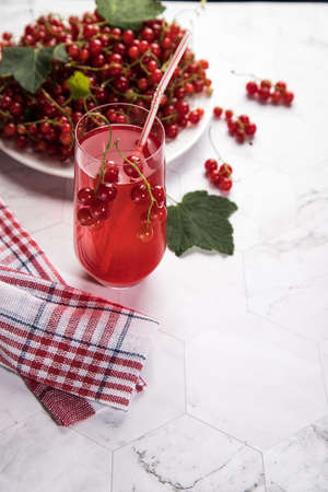 Sprigs of red currant berries are lying on a white plate, a berry Morse stands in a glass glass on a light background, next to a napkin in a red and white check. Summer drink that quenches your thirst Stock Photo
