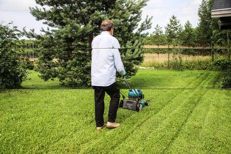 A man mows the grass on his own cottage plot Standard-Bild