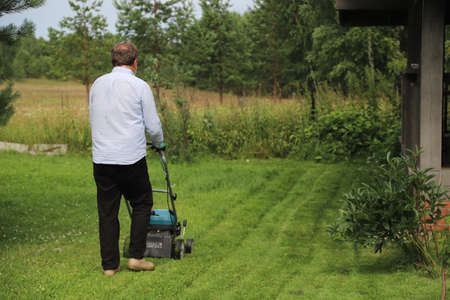 A man mows the grass on his own cottage plot