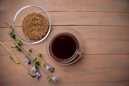 On a dark brown wooden background, a glass Cup with a chicory drink, a plate with chicory, a chicory flower. A place for a space mine .Horizontal orientation