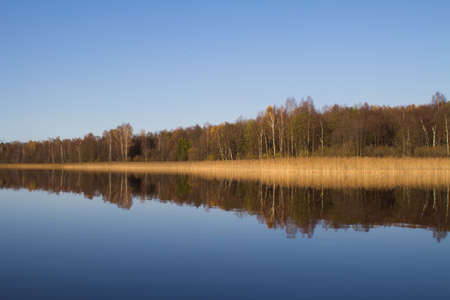The autumn forest is reflected in the lake water.The concept of a private holiday. Horizontal orientation