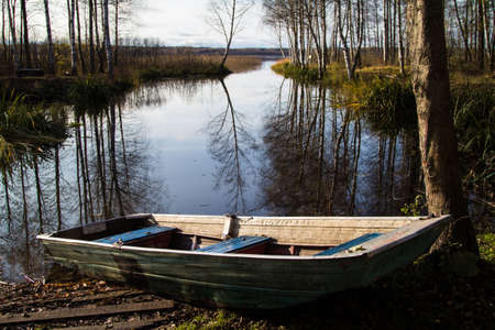 Empty boat on the riverbank in autumn. Trees without leaves are reflected in the water. Horizontal orientation