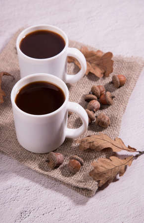 Glass coffee cups made of acorns on a napkin with acorns and oak leaves on a light background. Alternative to coffee, close-up. Copy space