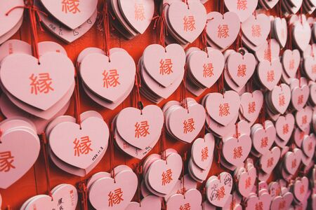 Octorbor 29, 2018 Japan, Inuyama City, Aichi Prefecture. Wooden Plate of ema by Heart shape of of Sanko Inari shrine. Pray for love. Фото со стока