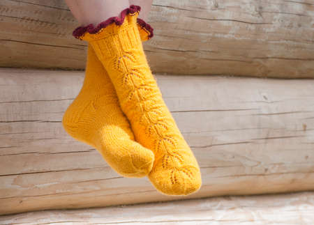 Legs of woman in knitted yellow socks in the sunlight