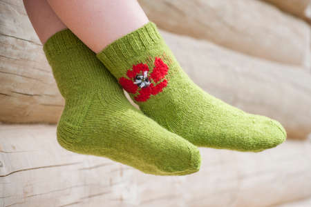 Legs of woman in knitted socks with poppy