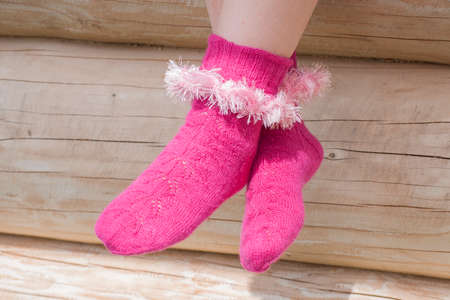 Legs of woman in knitted pink socks