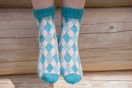 Pair of knitted socks in sunlight on background of log house