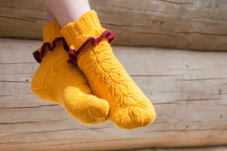 Pair of knitted yellow socks in sunlight
