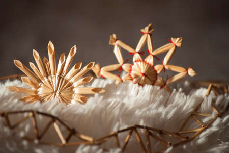 winter sunrise: Closeup with Christmas decorations- straw stars and string of reeds in sunlight Stock Photo