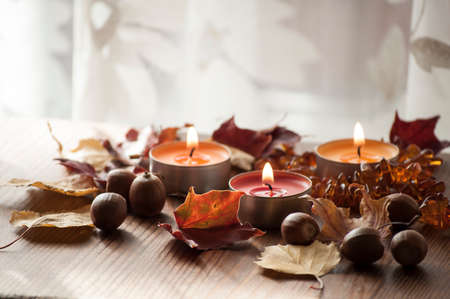 Closeup of burning candles, colorful autumn leaves and acorns of northern red oak and amber necklace on wooden board Stock Photo