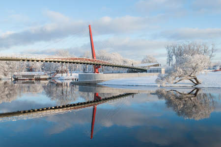 Winter landscape with footbridge across the river and beautiful reflection on water