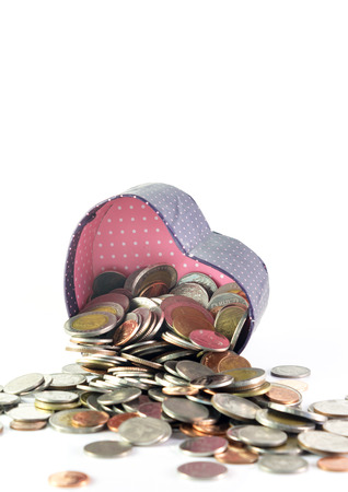 spilling: Isolated coins spilling from a heart box Stock Photo