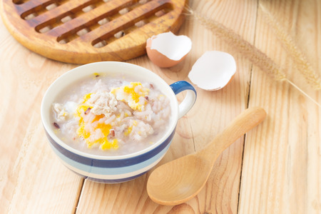 Traditional chinese brown rice gruel in white bowl, congee mixed with pork and eggs