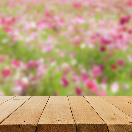 Defocus and blur image of terrace wood with flower field for background usage