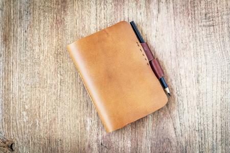 portadas de libros: cuadernos de cuero marrón sobre fondo de madera