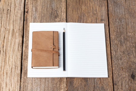 moles: Blank open notebook with black pencil on wood table,Business template mock up for adding your text