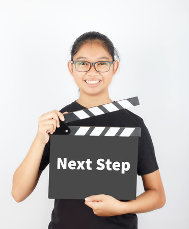the next step: NEXT STEP, message on slate film show by Asian girl Stock Photo
