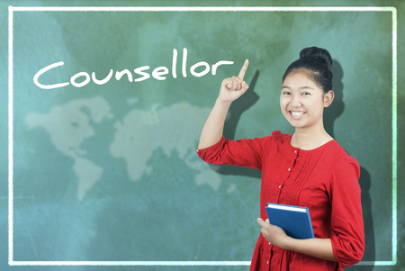 counsellor: The word Counsellor and cute Asian girl against chalkboard