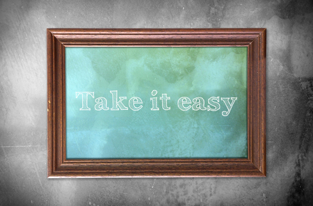 take it easy: Picture frame with word of Take it easy cement wall background