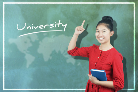 university word: The word University and cute Asian girl against chalkboard