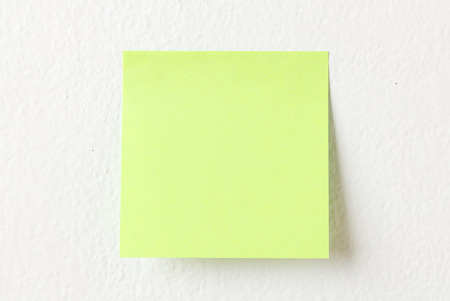 noteboard: Yellow note pad on white wall background