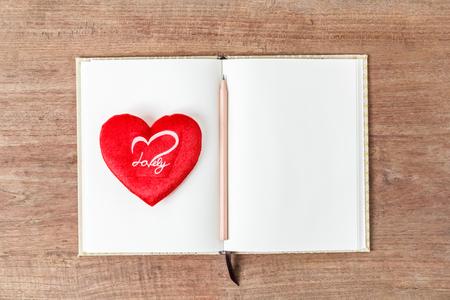 lunares rojos: cuaderno abierto en blanco con corazón rojo, modelo del asunto maqueta para agregar su texto, el enfoque selectivo