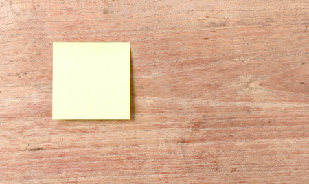 noteboard: Yellow note pad on wooden wall background