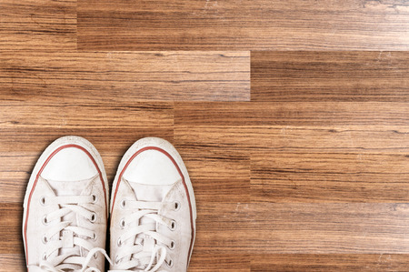 wooden floors: White sneakers from an aerial view on wooden floors. Top view. Stock Photo
