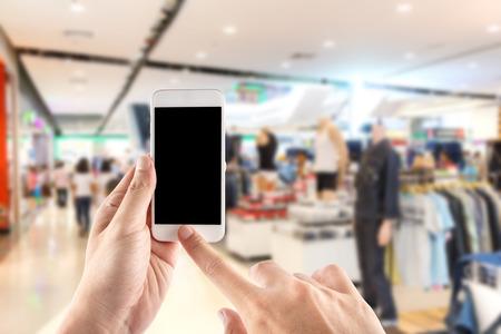 Chiuda sulla mano facendo uso dello smartphone in un mercato o in un grande magazzino