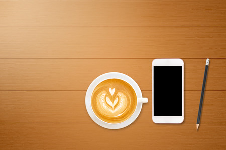 beverage display: Mobile phone with coffee cup on wooden table background