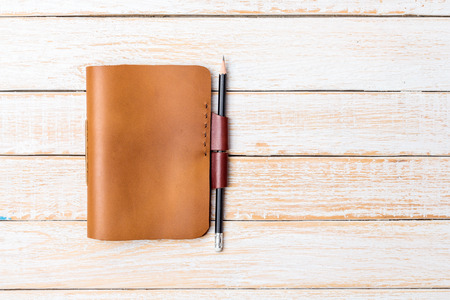 meeting agenda: Brown Leather notebooks with pencil on white wooden background Stock Photo