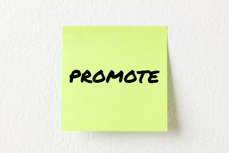 promote: Yellow note paper with words Promote on the white wall