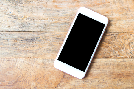 Smart phone on wooden table background with copy space, this has clipping path
