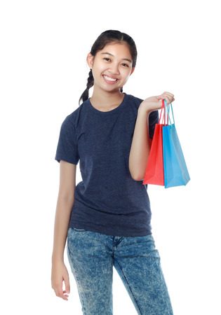 Shopping woman happy smiling holding shopping bags isolated on white background. Lovely fresh young mixed race Asian Caucasian female model