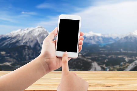 Hand using mobile smartphone in vertical position, blurred background - mockup template, this has clipping path
