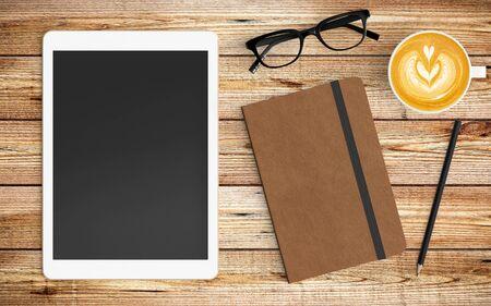 Moderner Arbeitsplatz mit Kaffeetasse, Papier, Notizbuch, Tablet oder Smartphone und Bleistiftkopierraum auf Holzhintergrund. Ansicht von oben. Flacher Lay-Stil. Standard-Bild