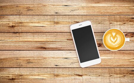 Modern workspace with coffee cup and tablet or smartphone copy space on wood background. Top view. Flat lay style.