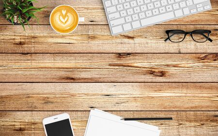 Modern workspace with coffee cup, paper, notebook, tablet or smartphone and keyboard copy space on wood background. Top view. Flat lay style.