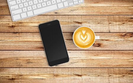 Modern workspace with coffee cup, notebook, tablet or smartphone and keyboard copy space on wood background. Top view. Flat lay style.
