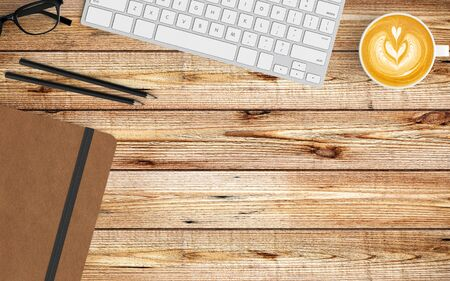 Modern workspace with coffee cup, notebook and keyboard copy space on wood background. Top view. Flat lay style. 스톡 콘텐츠