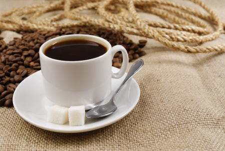 Cup of coffee with coffee beans on the table covered with a sackcloth photo