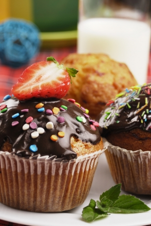 Three muffins with sprinkles on the plate with a glass of milk photo