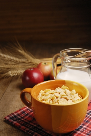 Bowl of cereals and the glass of milk on the wooden table photo