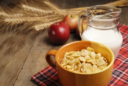 Bowl of cereals and the glass of milk on the wooden table Stock Photo - 15560671