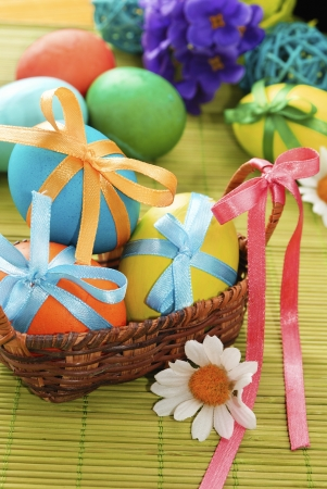 Colorful easter eggs in the basket on the green background photo