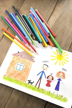kids drawing happy family near their house picture on the wooden table photo