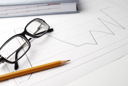 owe: Financial graphs, pencil and reading glasses Stock Photo