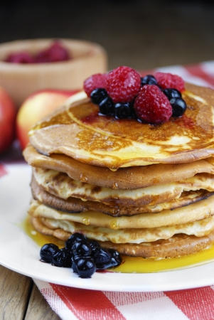 Pile of pancakes in the white plate on the wooden table photo